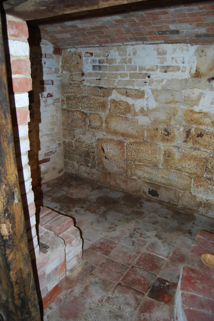 Cellar room with brick thralls, showing brick-vaulted ceiling, and ceramic floor tiles of probable 18th century date